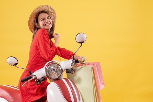 Vooraanzicht van gelukkige vrouw in rode jurk op bromfiets met boodschappentassen