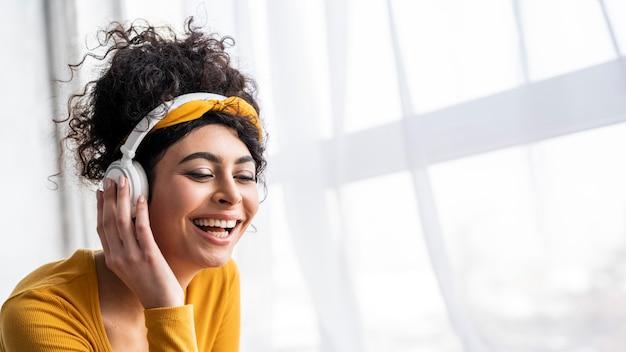Vooraanzicht van gelukkige vrouw lachen en luisteren naar muziek op koptelefoon met kopie ruimte