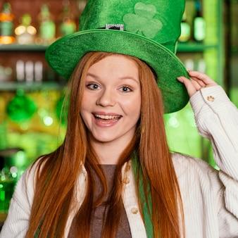 Vooraanzicht van gelukkige vrouw met hoed die st. patrick's day aan de bar