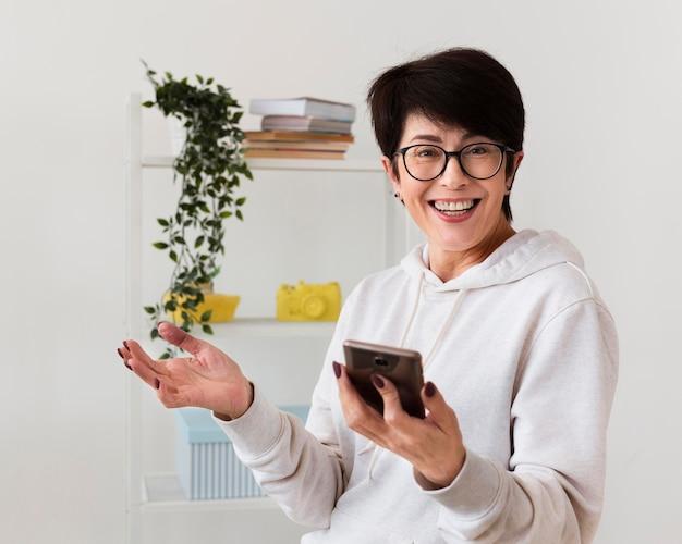 Vooraanzicht van gelukkige vrouw met smartphone