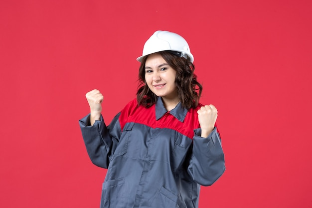 Vooraanzicht van gelukkige vrouwelijke bouwer in uniform met harde hoed op geïsoleerde rode achtergrond