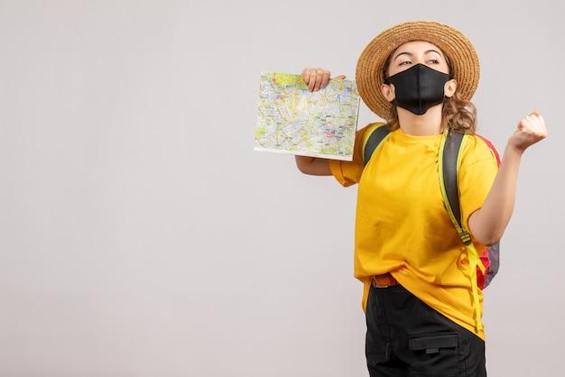 Vooraanzicht van gelukkige vrouwelijke reiziger met de zwarte kaart van de maskerholding op witte muur
