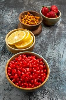 Vooraanzicht van gepelde granaatappels met ander fruit op donker-lichte tafelkleur vers fruit