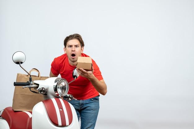 Vooraanzicht van geschokte bezorger in rode uniform staande in de buurt van scooter bestelling op witte achtergrond