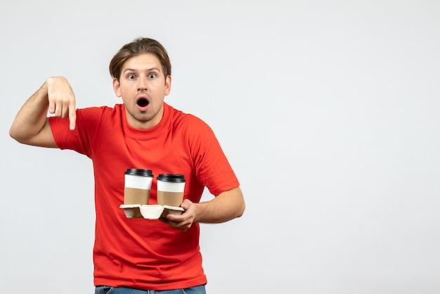 Vooraanzicht van geschokte jonge kerel in rode blouse die koffie in document bekers houdt en naar beneden wijst op witte achtergrond