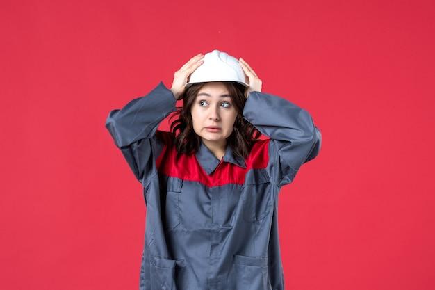 Vooraanzicht van geschokte vrouwelijke bouwer in uniform met helm op geïsoleerde rode achtergrond