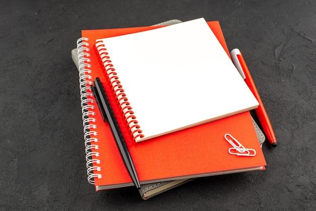 Vooraanzicht van gesloten spiraalvormige notitieboekjes in verschillende maten en pennen op zwart