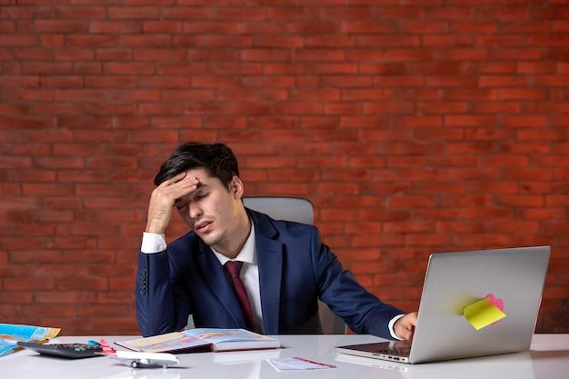 Vooraanzicht van gestresste reisagent die achter zijn werkplek in pak zit en laptop gebruikt bedrijfsbezettingsservice toerisme globaal agentschap assistent project