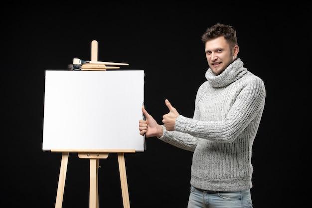 Vooraanzicht van getalenteerde mannelijke schilder met emotionele gezichtsuitdrukking die een goed gebaar maakt op zwart
