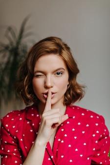 Vooraanzicht van geweldige vrouw in pyjama lippen met vinger aan te raken. binnen schot van onbezorgde vrouw in nachtkleding die stilte teken tonen.