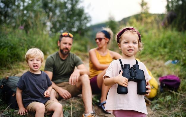 Vooraanzicht van gezin met kleine kinderen die buiten in de zomer natuur wandelen, zitten en rusten.