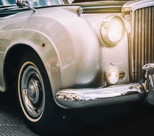 Vooraanzicht van glanzende metalen klassieke oldtimer. retro toned briefkaart, poster.