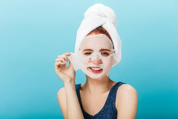 Vooraanzicht van glimlachend meisje gezichtsmasker opstijgen. studio shot van zalige vrouw met handdoek op hoofd poseren op blauwe achtergrond.
