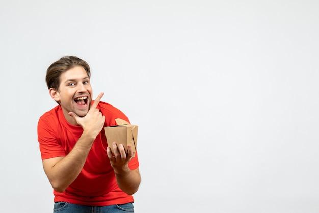 Vooraanzicht van glimlachende jonge kerel die in rode blouse kleine doos op witte achtergrond houdt