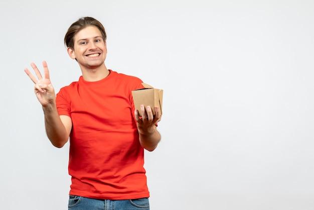 Vooraanzicht van glimlachende jonge kerel in rode blouse die kleine doos houdt die drie op witte achtergrond toont