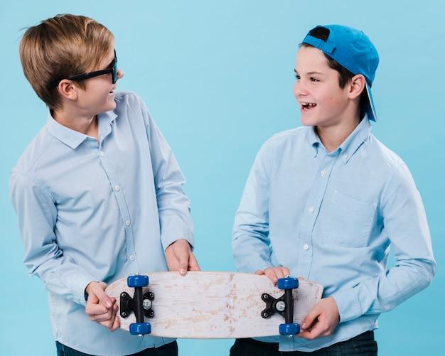 Vooraanzicht van glimlachende jongens die een skateboard houden