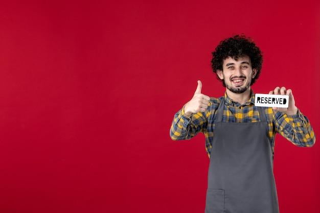 Vooraanzicht van glimlachende man-kelner met krullend haar die een gereserveerd pictogram vasthoudt en een goed gebaar maakt op geïsoleerde rode achtergrond