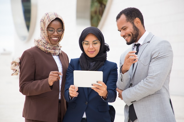 Vooraanzicht van glimlachende managers die tablet in openlucht gebruiken