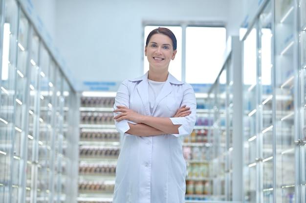 Vooraanzicht van glimlachende tevreden aantrekkelijke vrouwelijke apotheker poseren voor de camera op de werkplek