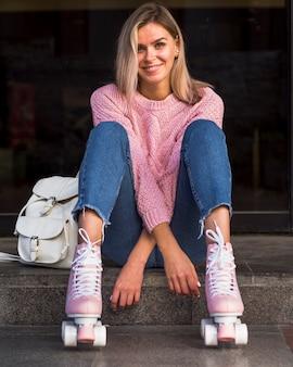 Vooraanzicht van glimlachende vrouw in rolschaatsen