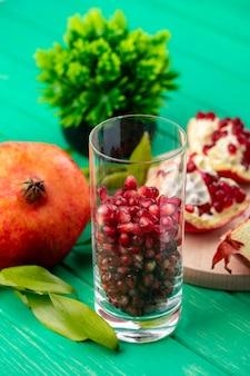 Vooraanzicht van granaatappelbessen in glas met gehele granaatappelstukken en bloemen op groene oppervlakte
