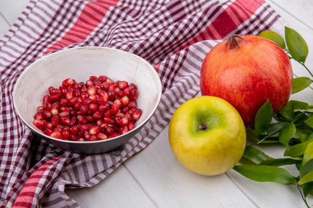 Vooraanzicht van granaatappelbessen in kom op plaiddoek met gehele en appel met bladeren op houten oppervlakte