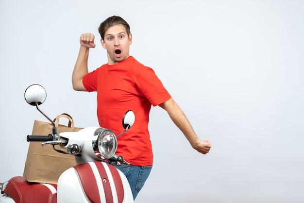 Vooraanzicht van grappige gekke emotionele bezorger in rode uniform staande in de buurt van scooter op witte achtergrond