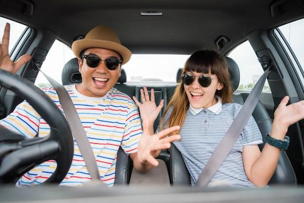 Vooraanzicht van grappige moment paar aziatische man en vrouw zitten in de auto. genieten van reisconcept.