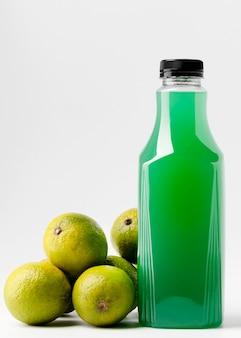 Vooraanzicht van groene sapfles met limoenen