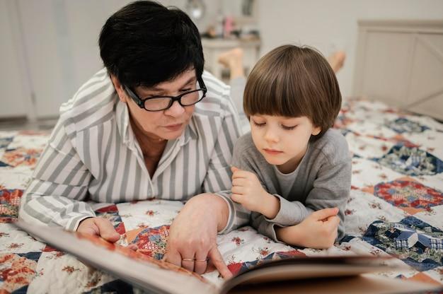 Vooraanzicht van grootmoeder en kleinzoon die thuis samen lezen