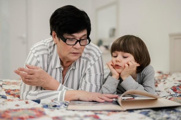 Vooraanzicht van grootmoeder en kleinzoon thuis lezen