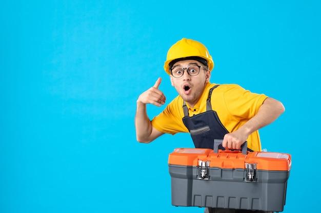 Vooraanzicht van haastige mannelijke werknemer in geel uniform met gereedschapskist op blauwe ondergrond