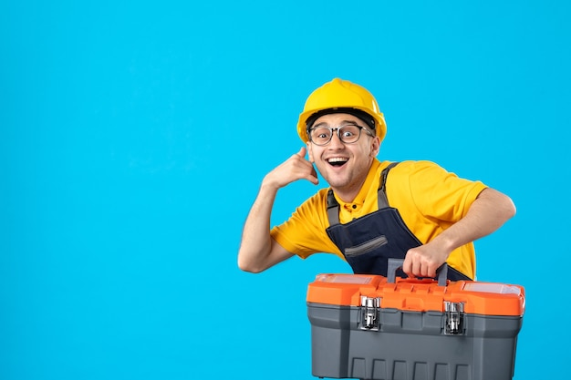 Vooraanzicht van haastige mannelijke werknemer in gele uniforme dragende gereedschapskist op blauwe muur