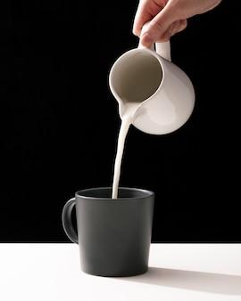 Vooraanzicht van hand gieten melk in mok