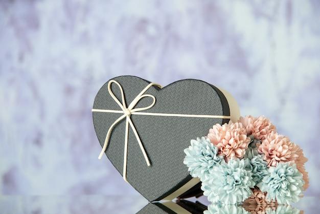 Vooraanzicht van hartdoos gekleurde bloemen op grijze abstracte achtergrondexemplaarruimte