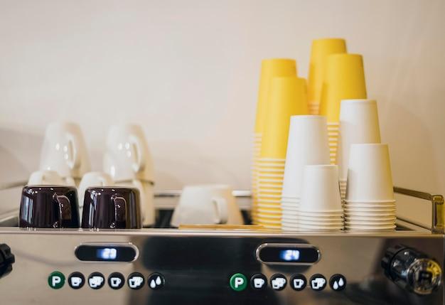 Vooraanzicht van heel veel kopjes en koffiezetapparaat