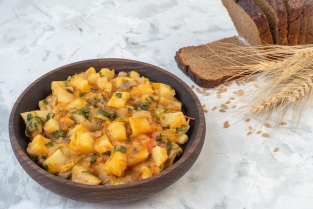 Vooraanzicht van heerlijk diner met aardappelen, groenten groen in een bruine kom en sneetjes brood op ijsachtergrond met vrije ruimte