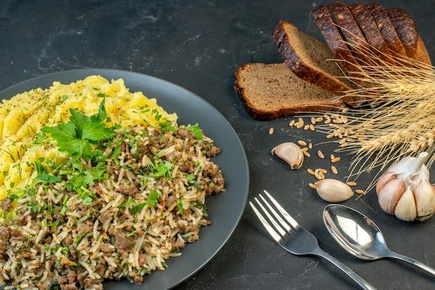 Vooraanzicht van heerlijk diner met vlees en aardappelpuree op een grijze plaat broodplakken knoflook spike bestek op zwarte achtergrond