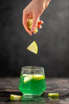 Vooraanzicht van heerlijk sap in een glazen hand die appellimoenen erin doet op een donkere achtergrond