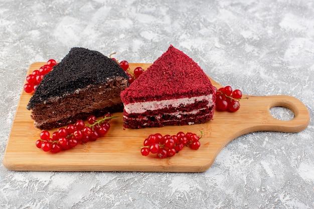 Vooraanzicht van heerlijke cakeplakken met roomchocolade en vruchten op het houten bureau