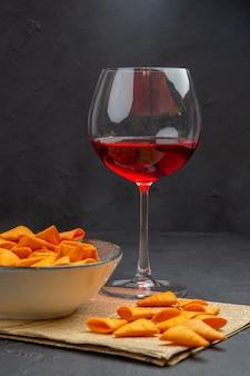 Vooraanzicht van heerlijke chips binnen en buiten de kom en rode wijn in een glas op een oude krant