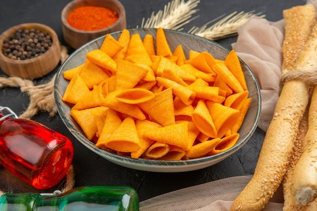 Vooraanzicht van heerlijke chips gevallen flessen, paprika's op handdoek en touw op een zwarte achtergrond