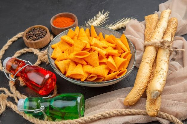 Vooraanzicht van heerlijke chips gevallen flessen paprika's op handdoek en touw op een zwarte achtergrond