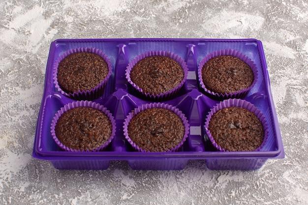 Vooraanzicht van heerlijke chocolade brownies in paarse stand op het lichte oppervlak