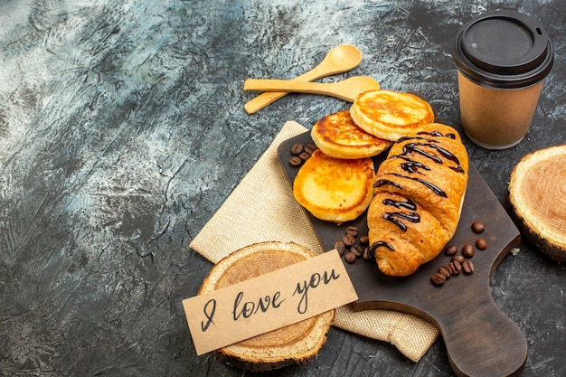 Vooraanzicht van heerlijke croissant pannenkoeken koffie voor geliefde aan de linkerkant op donkere achtergrond