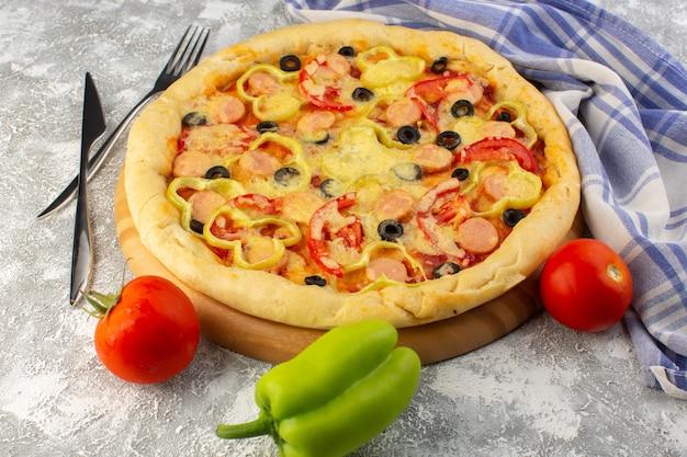 Vooraanzicht van heerlijke kaasachtige pizza met olijven, worstjes en tomaten