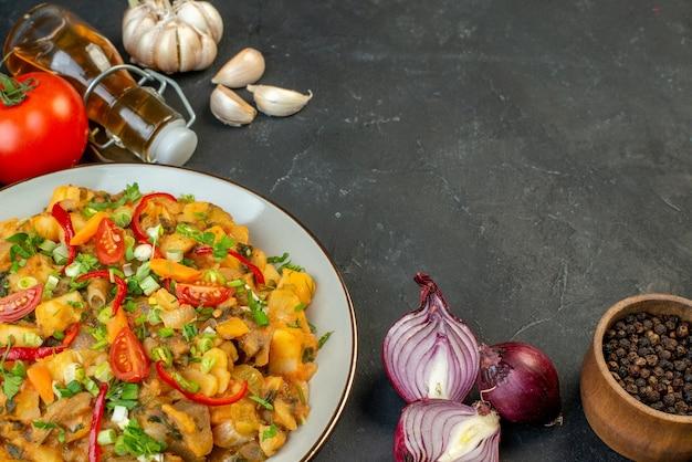 Vooraanzicht van heerlijke maaltijd op rode gestripte handdoek en verse groenten gevallen oliefles peper op zwarte achtergrond
