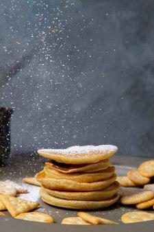 Vooraanzicht van heerlijke pannenkoeken met crackers op het grijze oppervlak