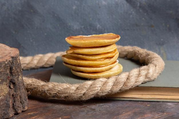 Vooraanzicht van heerlijke pannenkoeken met touwen op het grijze oppervlak