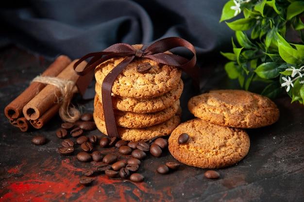 Vooraanzicht van heerlijke suikerkoekjes en koffiebonenbloempot op donkere achtergrond van mixkleuren
